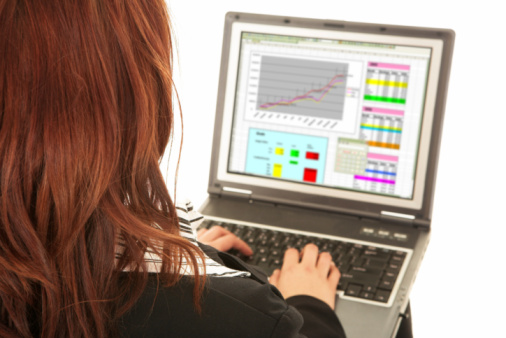 Redheaded businesswoman working on notebook computer. View from over her shoulder with a white background. Focus on the shoulder, screen blurred