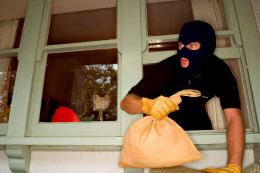 A stock Photograph of aáburglar robbing a house wearing a balaclava.á